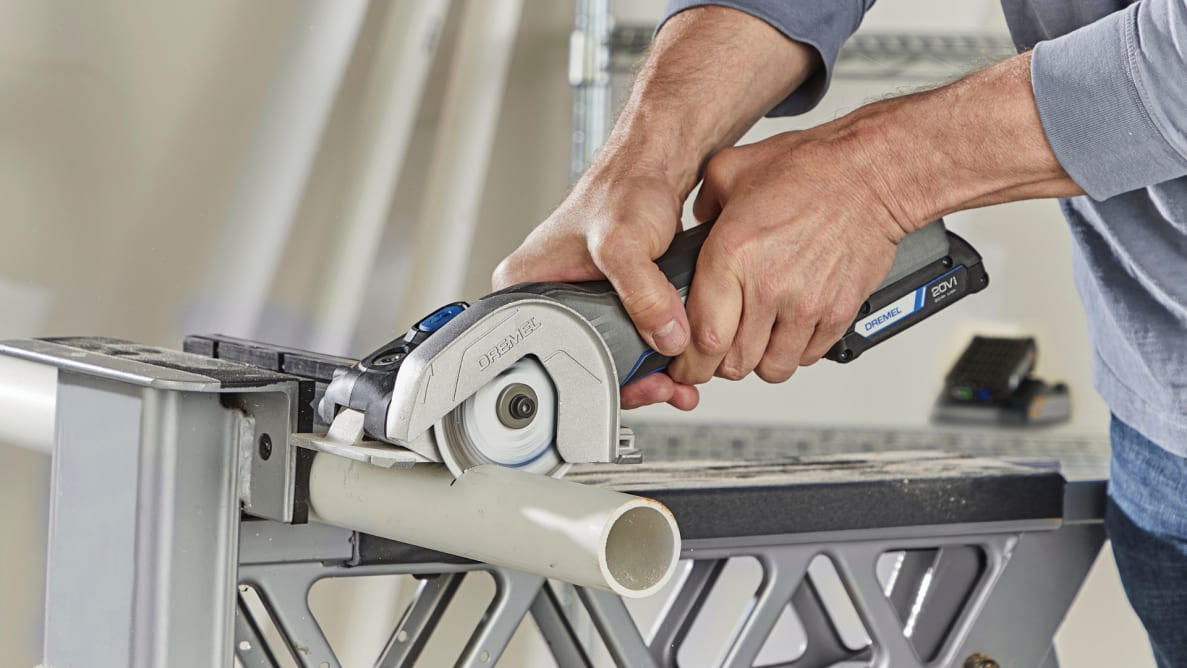 A person cuts a piece of pipe with the Dremel US20V Ultra-Saw.