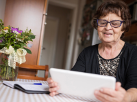 A senior looks at a digital tablet at home.
