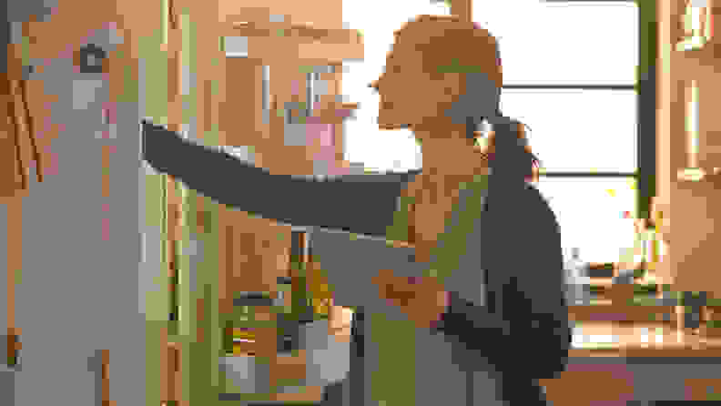 A woman inspects her fridge to make sure it's set up and ready for regular use.