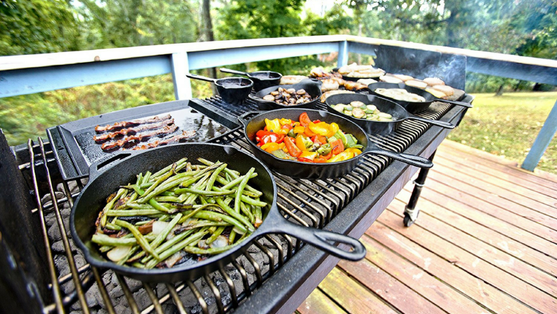 A series of Lodge cast iron skillets on a gas BBQ.