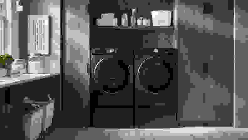The Samsung DVE45R6300V standing besides a Samsung washer in a brown laundry room.