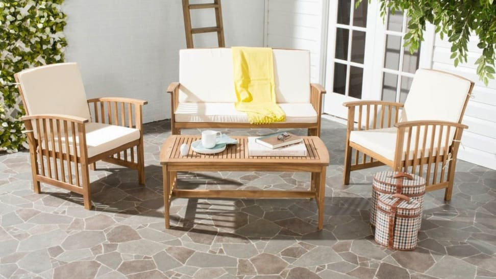 A set of Safavieh wooden patio furniture with white cushions is arranged on an outside patio.