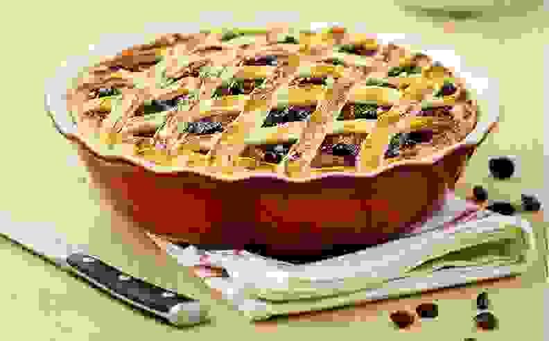 A latticed pie in a red pie dish.