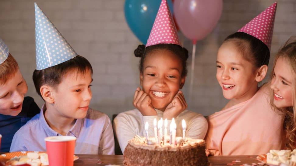 A happy Black girl smiles as her friends crowd around. She's ready to blow out birthday candles.
