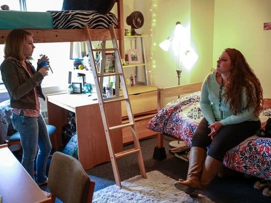 Mariah Whitelock, 18, of Riverview, right, a freshman at Oakland University in Rochester, chats with her roommate, Stephanie Campbell, 18, of Ortonville in their dorm room on Friday, Oct. 30, 2015.