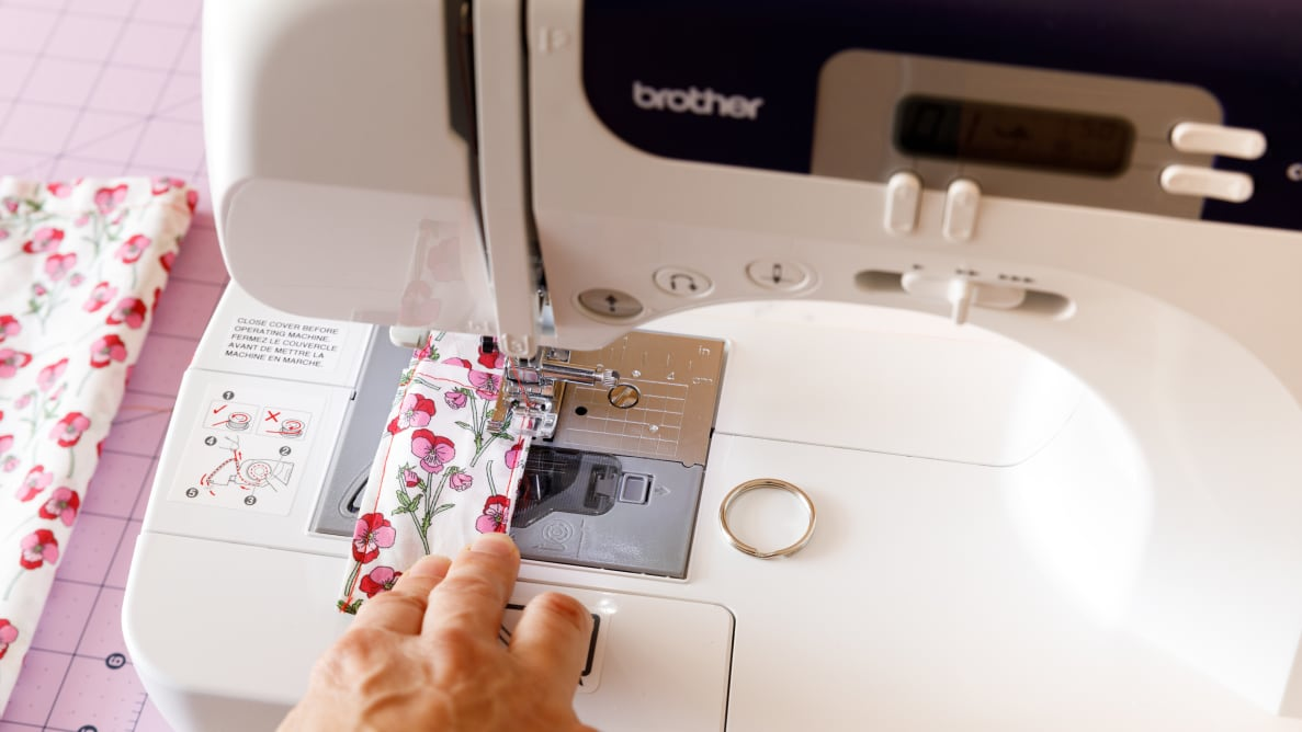 Close-up photo of the writer using a sewing machine.