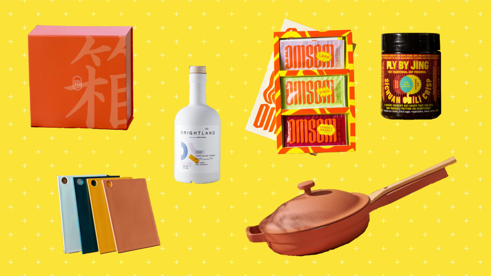 Clockwise from the left: An orange box of Bokksu Japanese snack subscription box, a bottle of Brightland olive oil, a pack of three Southeast Asian sauce kits by Omsom, a jar of Fly By Jing chili crisp, a Terracotta color Always pan, and three cutting boards from Material.