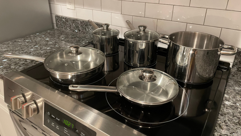 Stainless steel pots and pans resting on an electric cooktop.