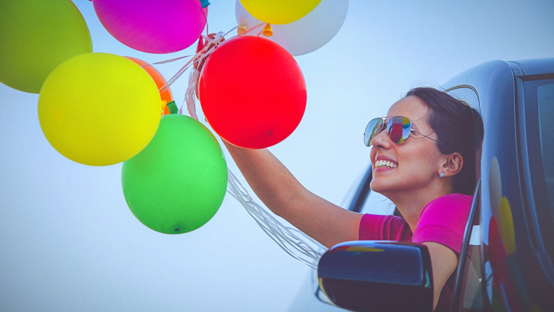 A woman smiles as she hangs out of a car window with colorful balloons