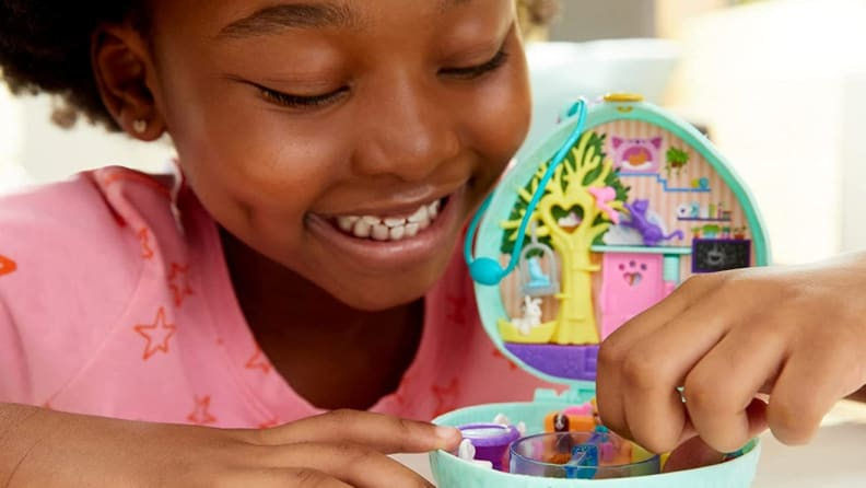 Young child playing with small Polly Pocket toy.