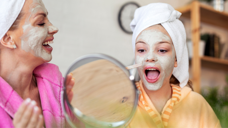 Mother and daughter with face masks and towels on their head having a spa day