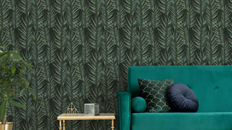 A dark freen leaf print wallpaper is pasted on the walls. A teal couch sits in front of the wallpapered wall.