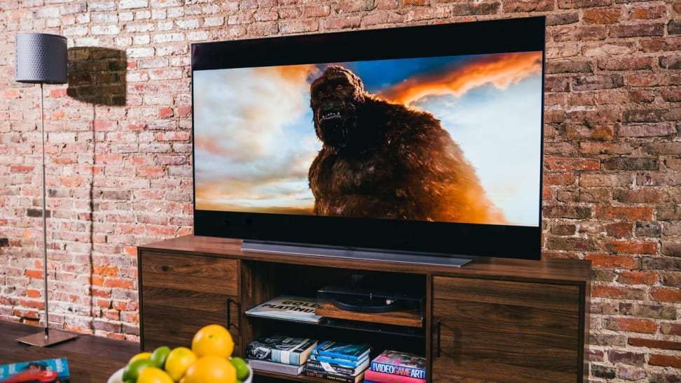 Flat screen smart TV playing movie in front of brick wall.