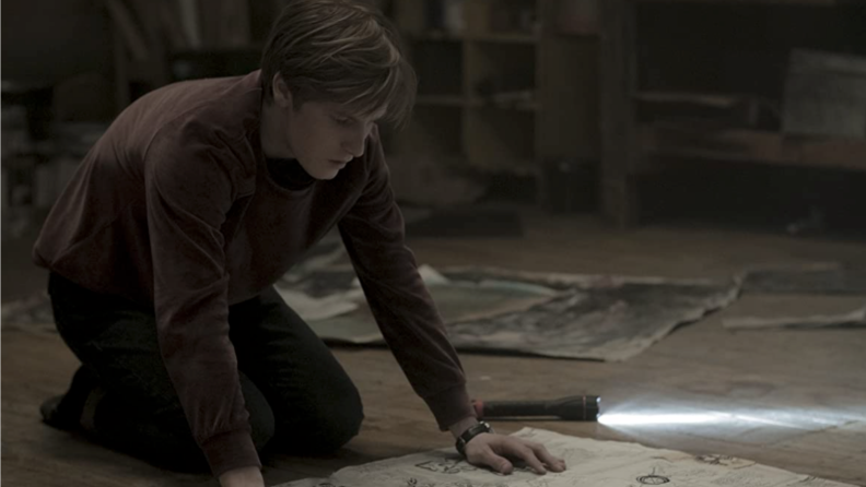A still from 'Dark' featuring a young man kneeling over a map on the floor.