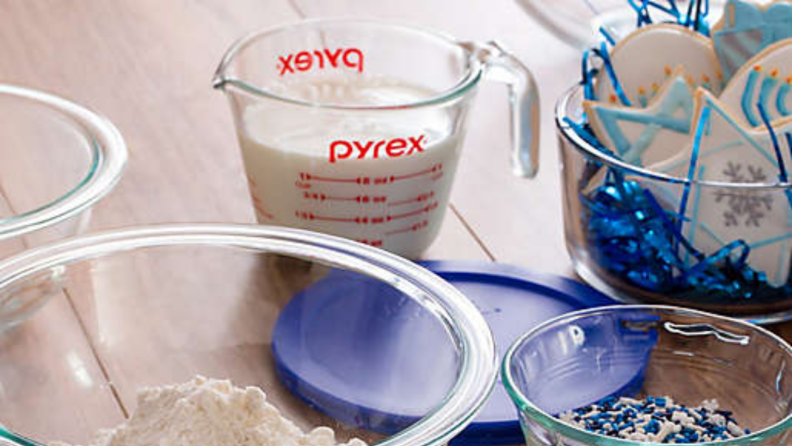 An image of a Pyrex measuring cup as seen through the rims of two glass bowls. The cup sits on top of a blue bowl lid.