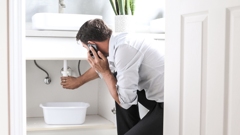 Person looking at leaking piped under sink.