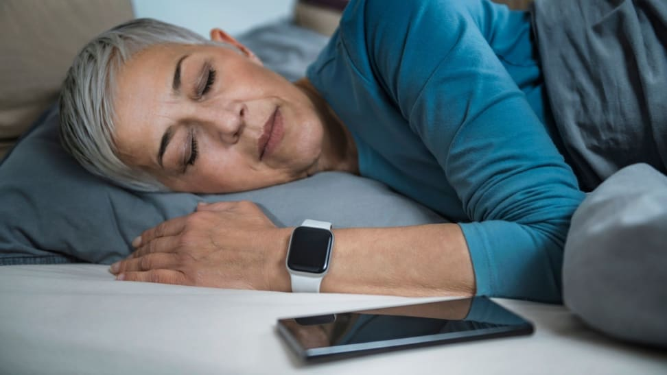 Someone sleeps wearing a sleep tracking wearable on their wrist with their phone beside them