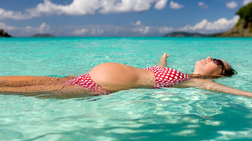 Pregnant woman floating in ocean