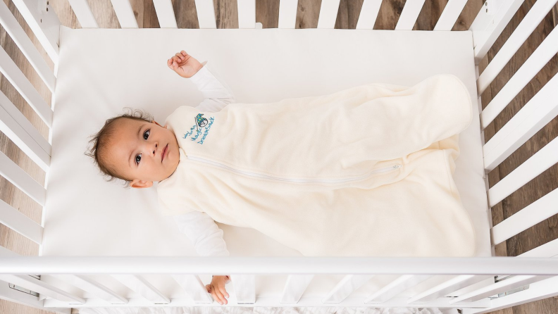 A baby wearing a cream onesie lays in a crib.