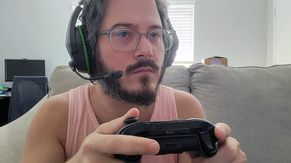Man wearing the HyperX CloudX Stinger Core while holding an Xbox controller