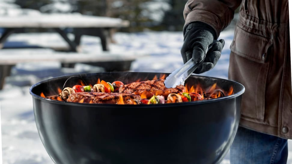 Outdoor grill in the wintertime with gloved hand using tongs to flip meat and vegetable skewers