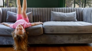 A young girl hanging upside down on a couch