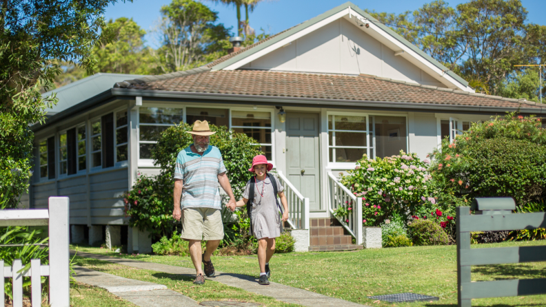 A grandparent and grandchild hold hands while walking outside the home.