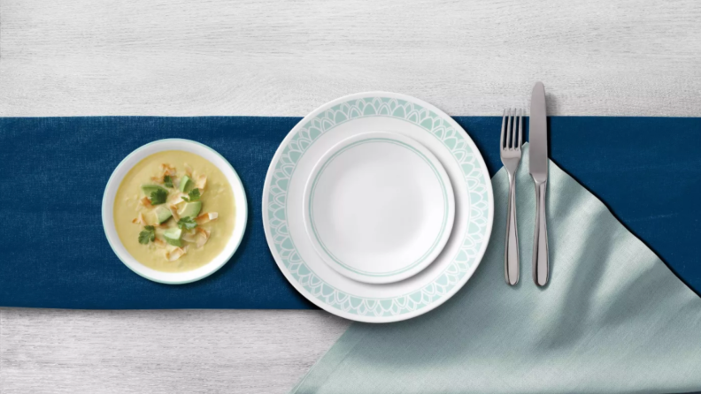 Two empty white and aqua colored plates stacked together next to bowl of soup and silverware.