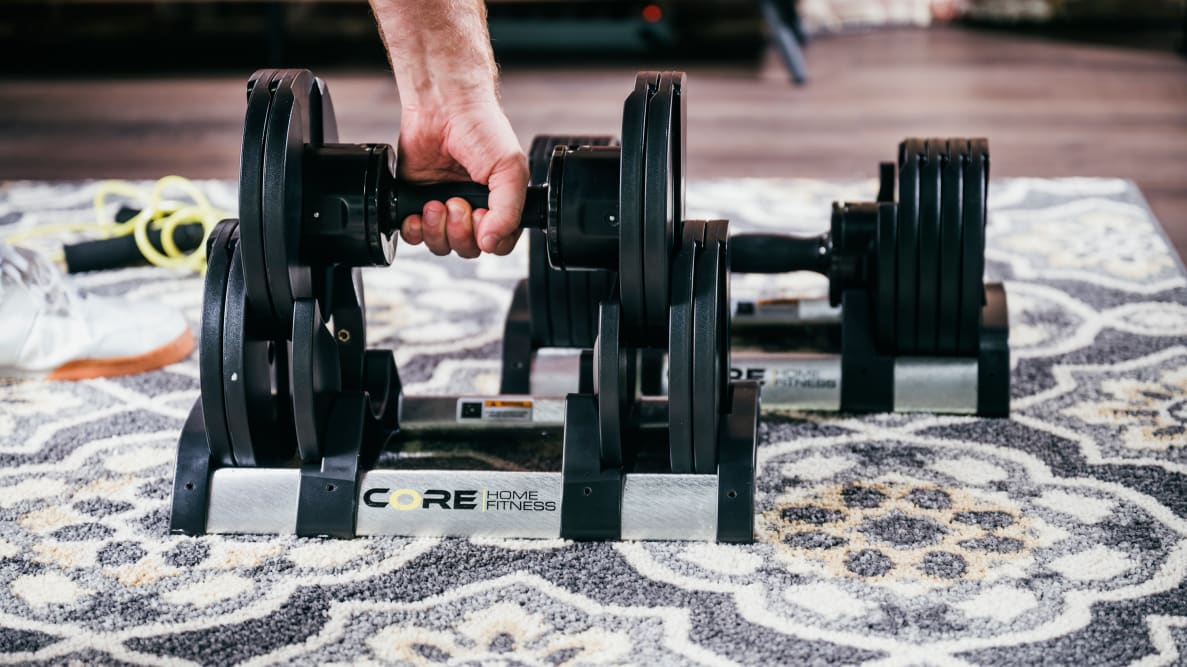 A hand lifting a pair of adjustable dumbbells out of their tray.