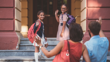 Two young girls on the steps of a school waving to their parents in the foreground