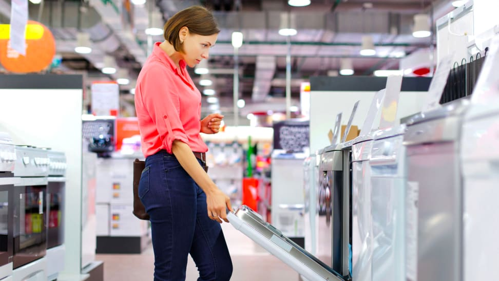 A woman examines a dishwasher in a department store.