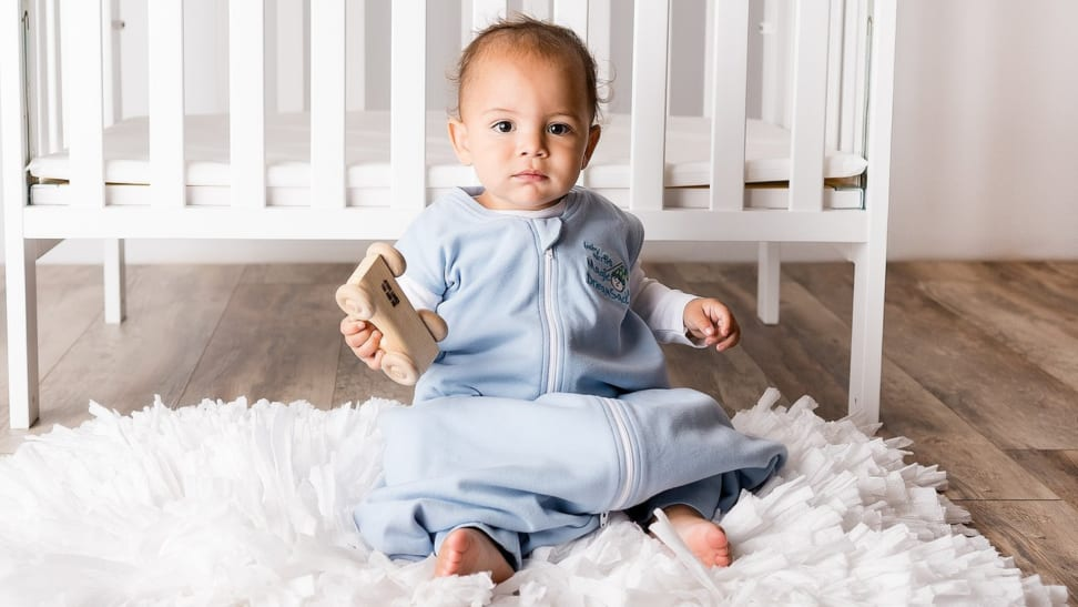 An infant wearing a blue Magic Merlin's Magic Dream Sack sits in front of a crib.