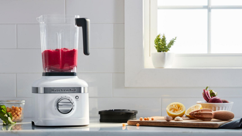 The k400 KitchenAid blender is on the kitchen counter, surrounded by fruits and vegetables.