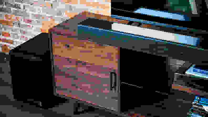 The all black Sony HT-A7000 sits atop a dark wood console against a brick wall below a large flat screen TV next to a large black subwoofer as shot from the right.