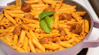 A pot of manicotti pasta cooked in tomato sauce with meatballs in an Always pan.