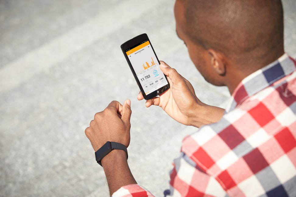 A man wearing the Withings Pulse O2 and looking at the Health Mate app