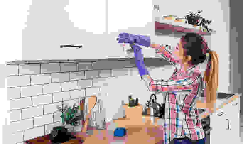 Woman wiping cabinets