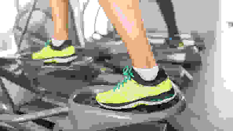A close-up of someone's feet on an elliptical machine.