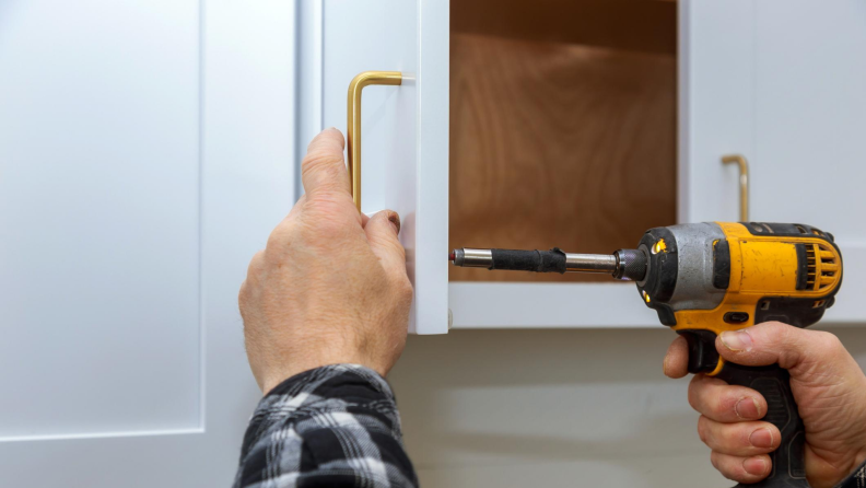 Man installing a new cabinet knob with a drill