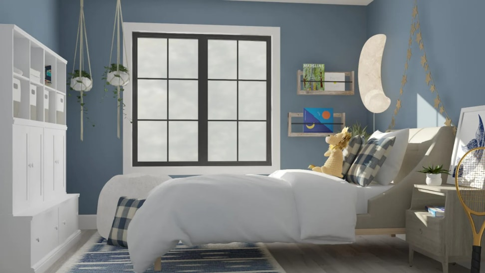 A big kid room with a large bed, blue walls, and big bright window