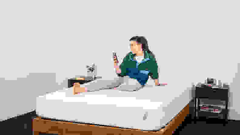 a person sits on their phone atop the Tuft & Needle Original