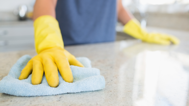 Hands with yellow gloves holding blue cleaning towel scrubbing countertop