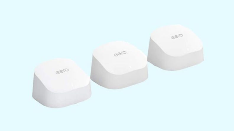 Three white Amazon Eero mesh wi-fi systems lined up next to each other in front of blue background