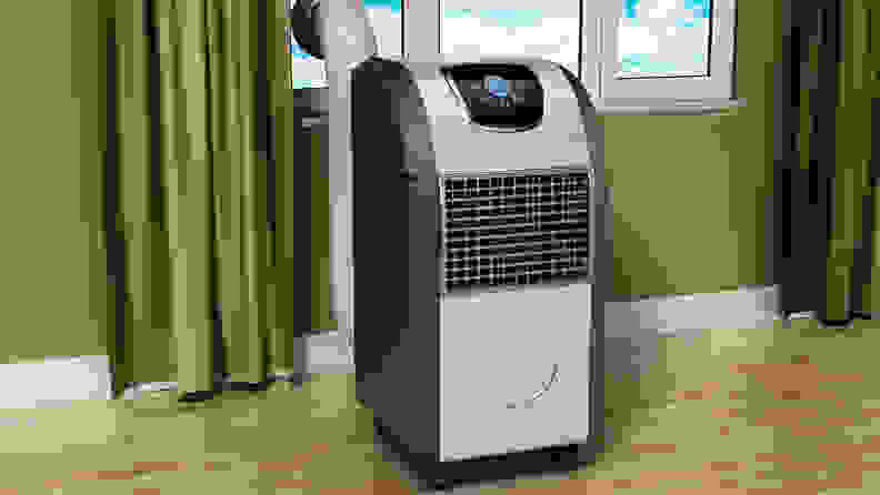 A portable air conditioning unit in front of a window.