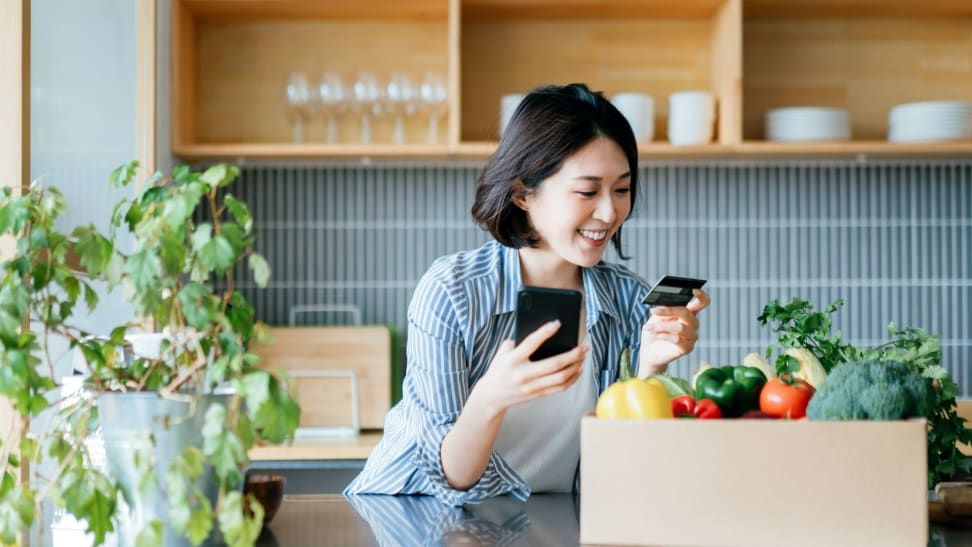 Woman holding cell phone and credit card while  standing over box of groceries at kitchen island
