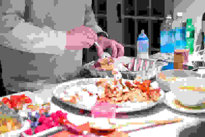 A man is putting away leftovers from a Thanksgiving day feast.  RM