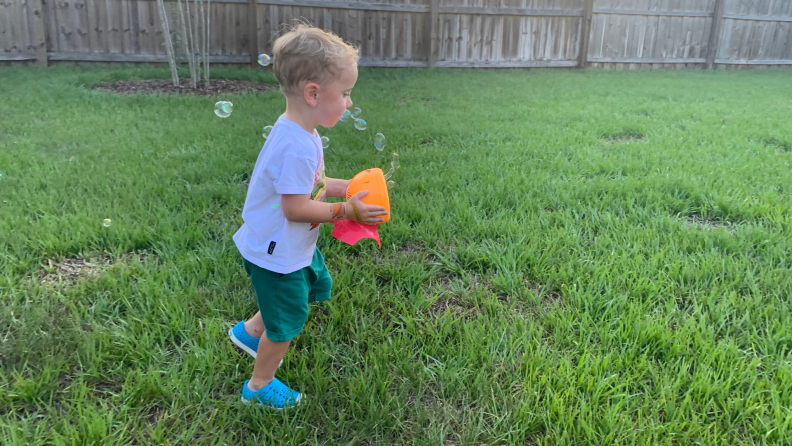 A toddler carries a bubble machine through the yard.