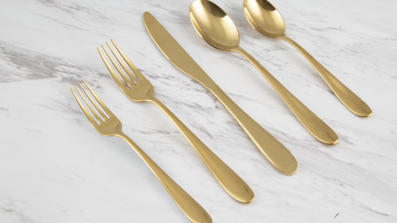 Golden flatware (knives, forks, spoons) sit together on a marble countertop.