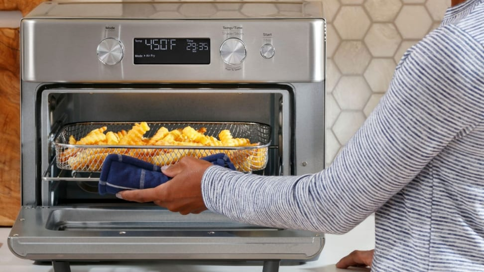 A woman removes a pan of French fries from GE's 8-in-1 Air Fryer Toaster Oven.