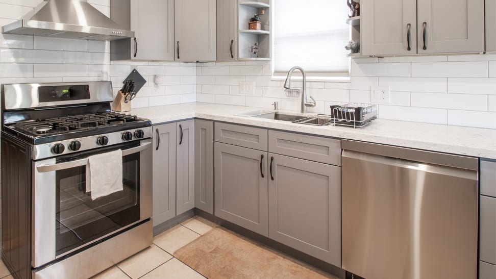 An array of appliances, including an oven, a dishwasher, and a range displayed on tiled floors in a kitchen.
